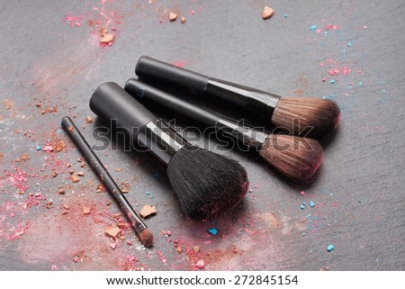 set of  make up brushes with make up crumbles  on black background - stock photo