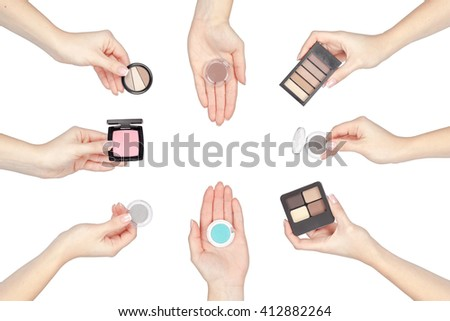 set of makeup products in a hands isolated on white background