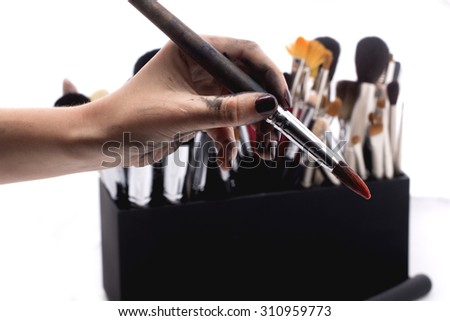 Set of many professional make-up brushes for eyeshadow powder and facial foundation for visagistes in black plastic box and human hand holding one brush on white background, horizontal picture