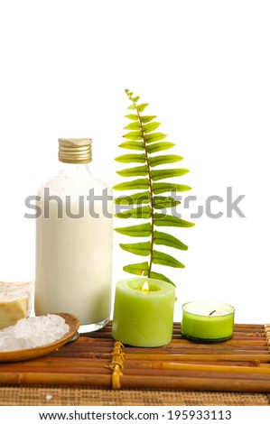 Set of massage oil and fern,candle,salt in spoon on bamboo mat