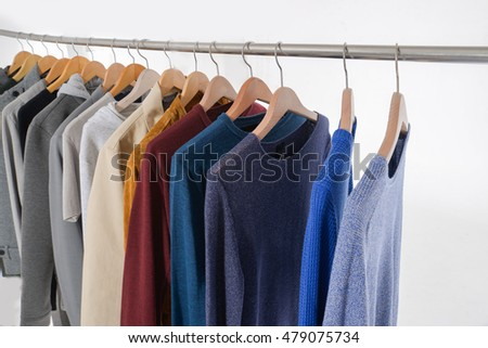Set of men's clothes of different colors ,coat on wooden hangers