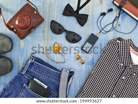 Set of men's clothing and accessories on blue wooden table. Hipster concept