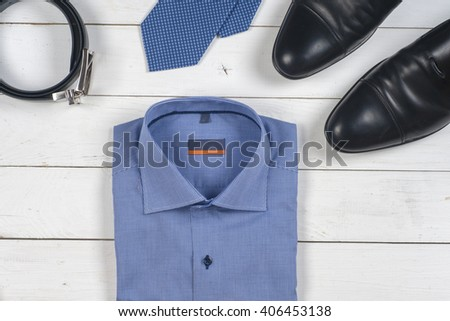 set of men's clothing and shoes on wooden background. Men accessories. Black elegant accessories pieces isolated on white wooden table. Top view. - stock photo