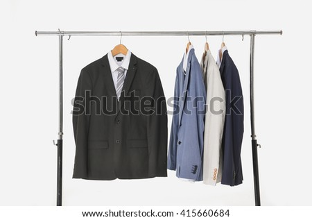 Set of men's suits hanging on a white background - stock photo