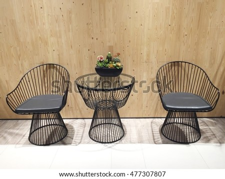 Set of metal chairs and desk with wooden wall background