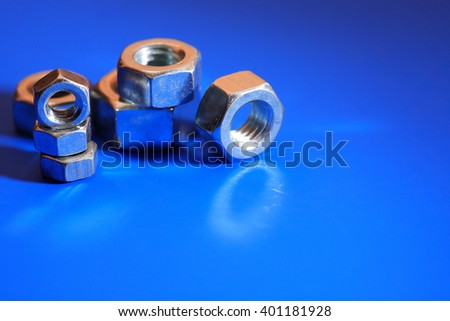 Set of metal nuts on blue background with shadow - stock photo
