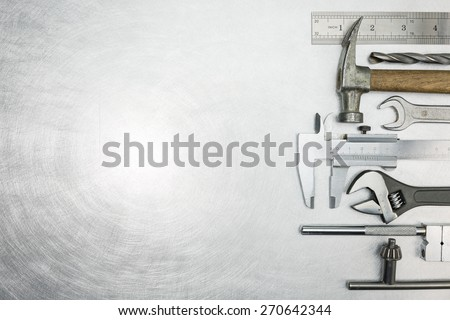 Set of  metal working tools on scratched background - stock photo