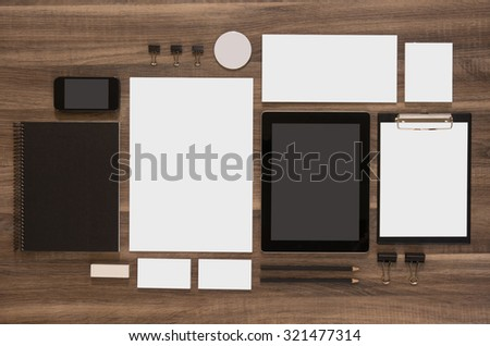 Set of mock-up business brand template on wooden desk. Set of stationery with black notepads and tablet. Mobile phone. - stock photo