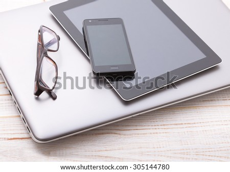 set of modern computer devices - laptop, tablen and phone top view close up - stock photo
