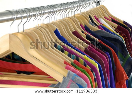 Set of multi colored shirts on hangers against a white