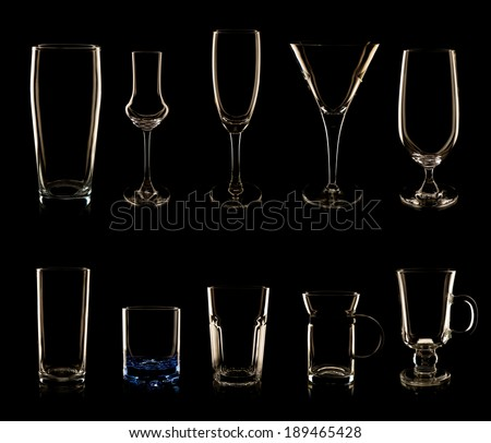 Set of multiple glasses and bottles shot in low-key lighting isolated over the black background - stock photo