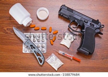 Set of narcotics and handgun on wooden table - stock photo