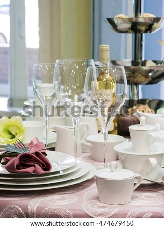 Set of new dishes on table with tablecloth. Stack of white plates and wine glasses on restaurant table. Shallow DOF. Vertical