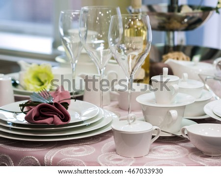 Set of new dishes on table with tablecloth. White plates and wine glasses on restaurant table. Shallow DOF