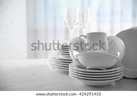 Set of new white dishes on wooden table, indoors - stock photo