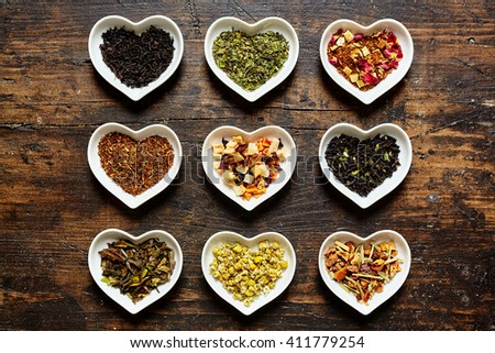 Set of nine assorted sorts of raw tea in tiny bowls shaped as hearts on weathered wooden surface - stock photo