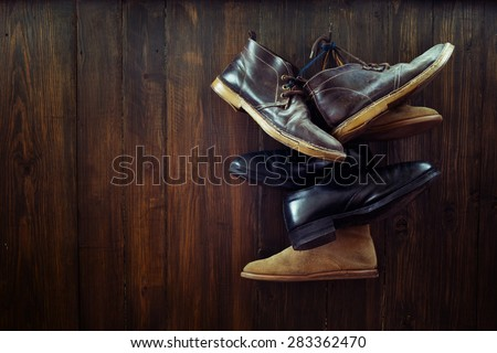 Set of old boots hanging on the nail on wooden board