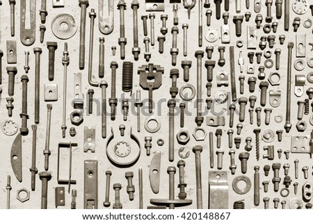 set of old rusty metal screws, nuts and bolts on a gray background. black and white photo. Flat lay, top view
