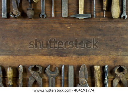 Set of old rusty tools on rustic wooden background with copy space in the middle. - stock photo