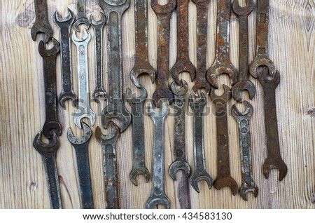 Set of old spanners. Rough spanners on wooden background. Frame of metallic tools