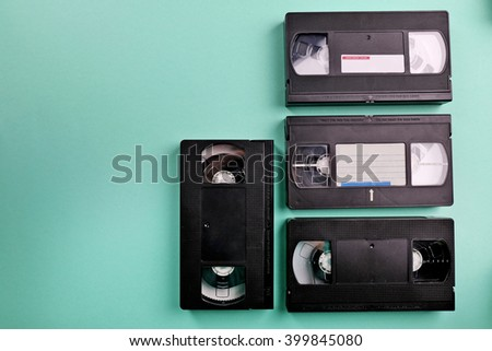 Set of old video cassettes on turquoise background