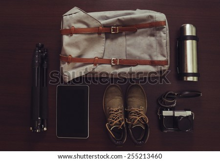 Set of outfit for tourism on wooden background, top view - stock photo