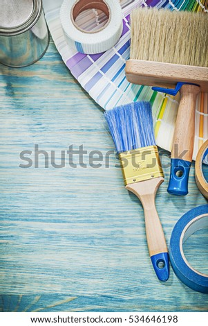 Set of paint cans brushes color sampler adhesive tape on wooden board.