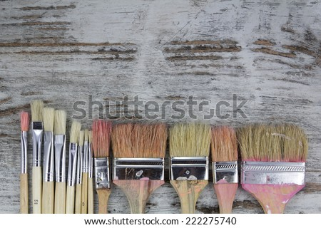 Set of paintbrushes in a wood background, vintage - stock photo