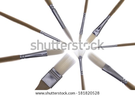 Set of paintbrushes of different sizes and shapes arranged in a radial pattern with their bristles converging in the centre and a high key bright flare effect on a white background - stock photo