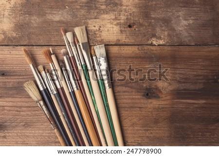 Set of paintbrushes on a wood background, tinted photo - stock photo