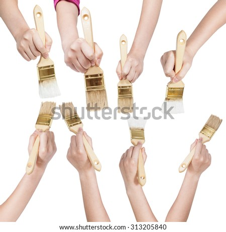 set of painter hands with flat paint brushes with clean and white painted tips isolated on white background - stock photo