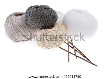 Set of pastel wool yarn wrapped in hanks and a pair of wooden double pointed knitting needles