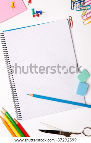 Set of pencils, erasers, post-its and other useful supplies for the school. There is a centered blank notebook for text writing - stock photo