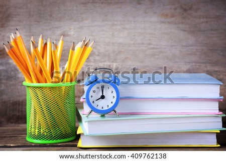Set of pencils in metal holder, stack of books and alarm clock on wooden background - stock photo