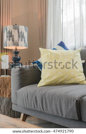 set of pillows on modern grey sofa in living room with lamp on wooden table side