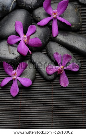 Set of pink orchid with zen black stones on bamboo stick straw mat - stock photo