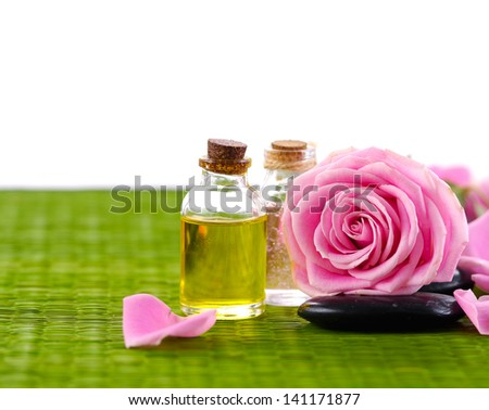 Set of Pink roses with petals and massage oil with stone on green mat