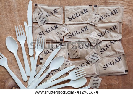 Set of plastic spoon with sugar salt and pepper packet on wood on the top of view