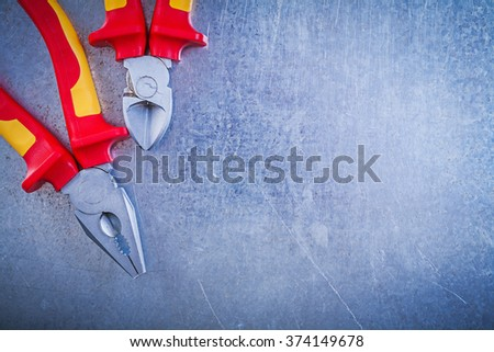 Set of pliers wire-cutter on metallic background electricity concept. - stock photo