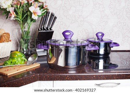 set of pots with plastic handles in the interior borscht soup wooden board knife kitchen countertops, atmosphere, domesticity, cooking process