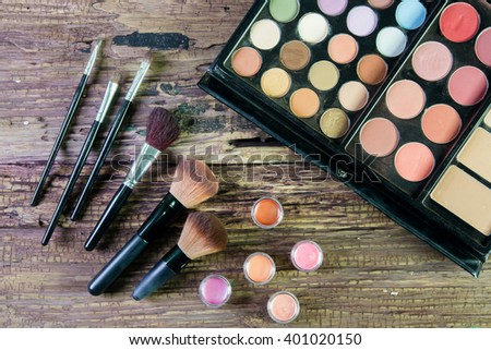 Set of professional brushes for a make-up of eyes, a palette of nude colored eyeshadows and colorful pigments on a wooden background. set of the professional makeup artist - stock photo