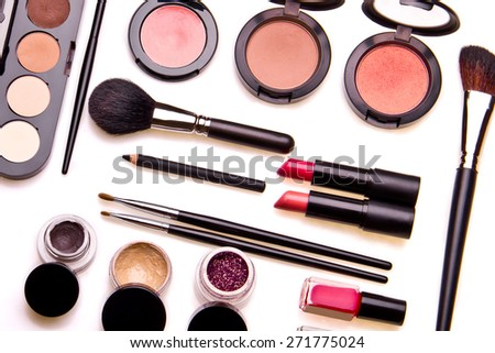 Set of professional cosmetic: make-up brushes, shadows, lipstick, nail polishes - partly isolated with shadows on white background. Overhead view. - stock photo