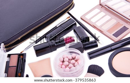 Set of professional cosmetic: make-up mascara, shadows, lipstick, nail polish - partly isolated with shadows on white background in random order. Overhead view.