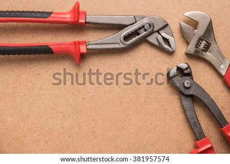 Set of pump plier, plier and wrenches. Tools over a wood panel. Top view with copy space. - stock photo