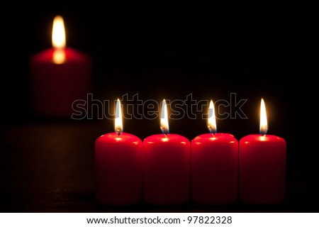 Set of red candles burning in the dark with selective focus