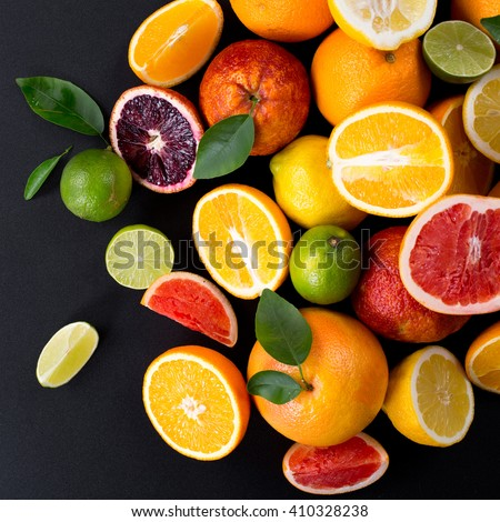 Set of ripe citrus fruit with leaves on a black background. Grapefruit, orange, lime, lemon, red orange. View from abov