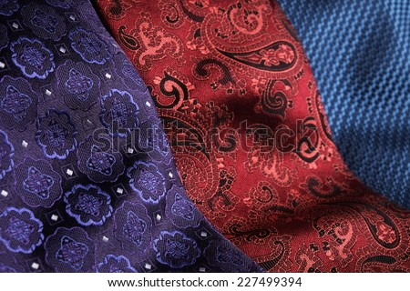 Set of rolled up silk ties close to each other, side-by-side. Blue, red, bordeaux, black and purple - stock photo