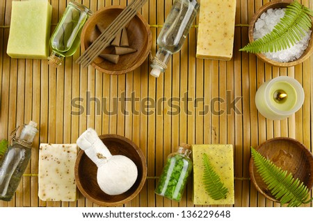 Set of row of Bar of natural handmade soap with fern ,salt in glass ,massage ball in bowl on wooden mat - stock photo