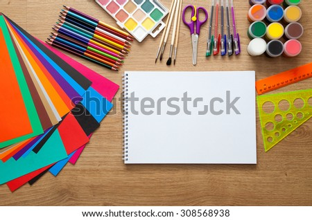 set of school supplies with pencil, colored pen, watercolor paint, notebook and scissors - stock photo