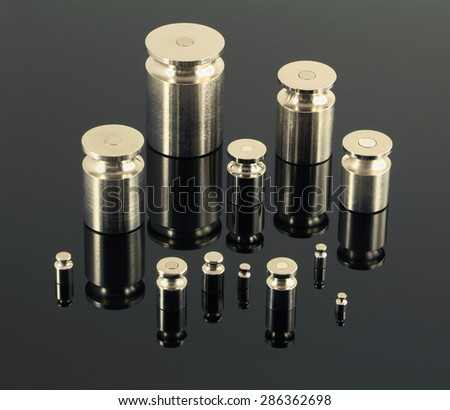 Set of shiny metal weights on dark mirror surface. Group of twelve objects.
